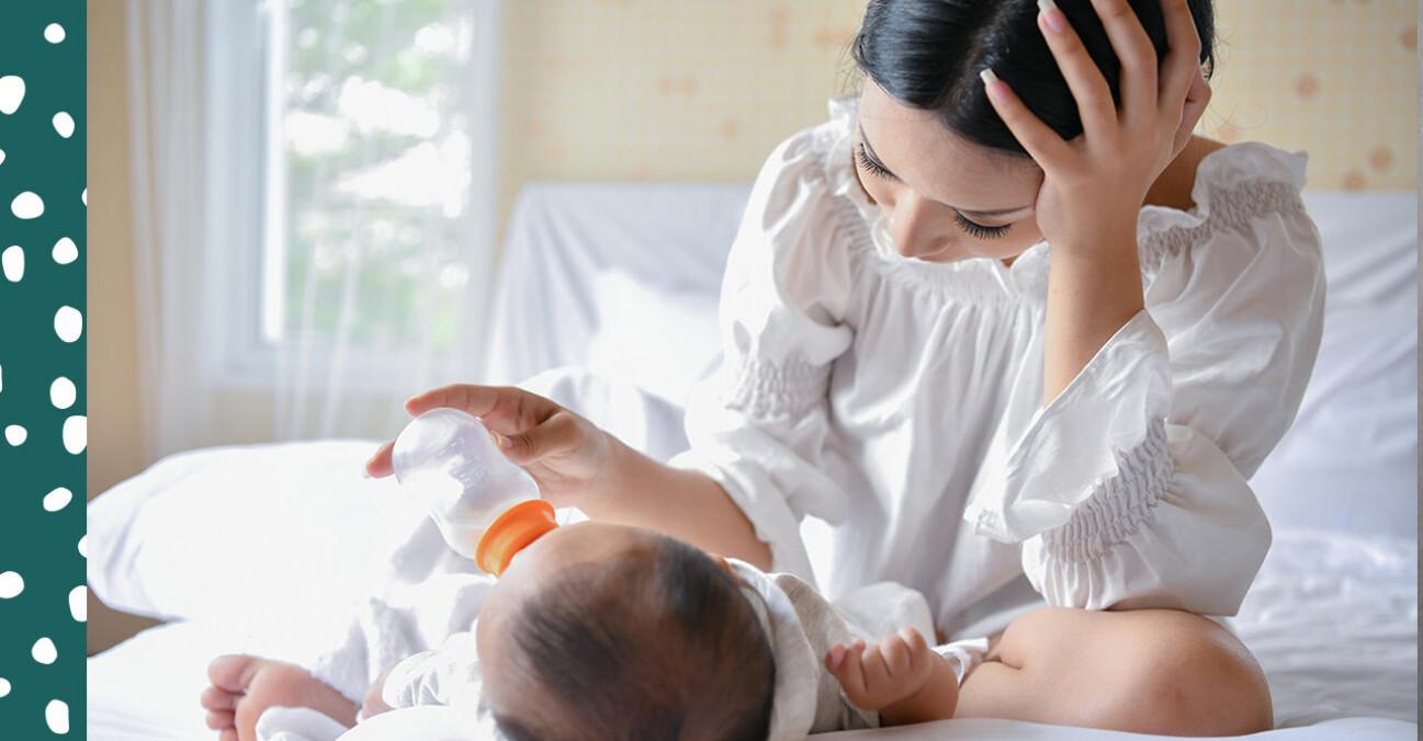 trött mamma flaskmatar bebis