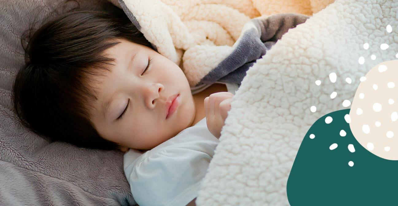 barn som sover under en filt