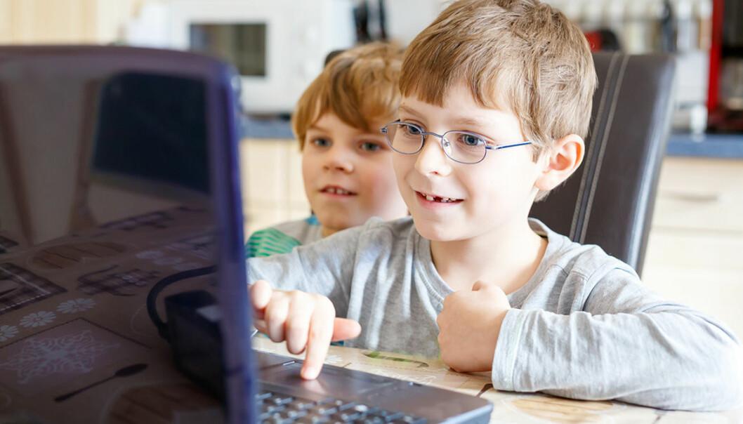 Två barn sitter framför en dator tillsammans