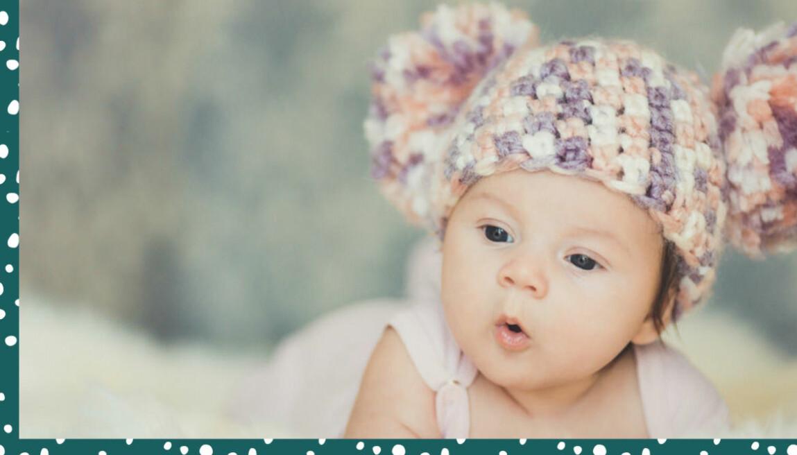 Bebis i stickad mössa med tofsar.