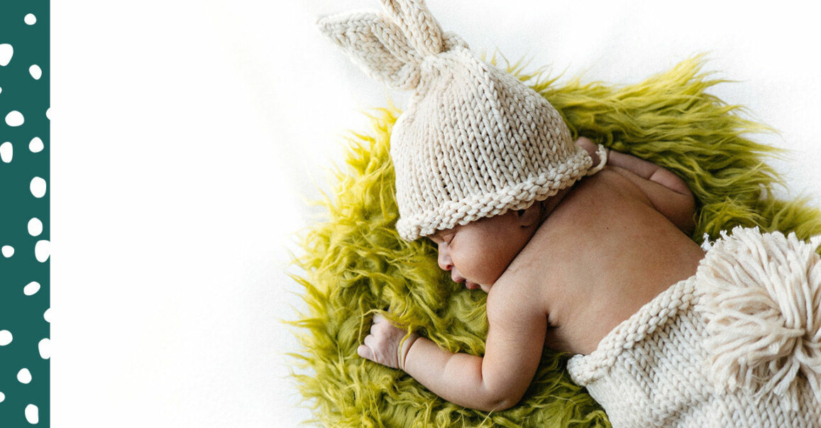 Bebis på grön matta i mössa med kaninöron.