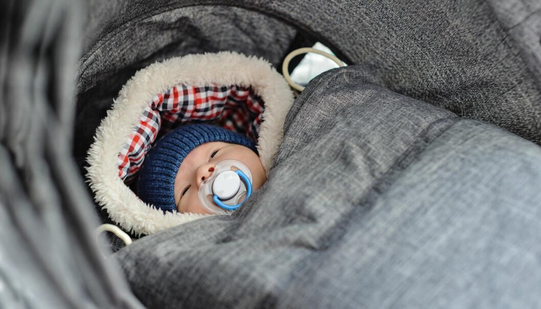 Bebis som är klädd för vintern i åkpåse