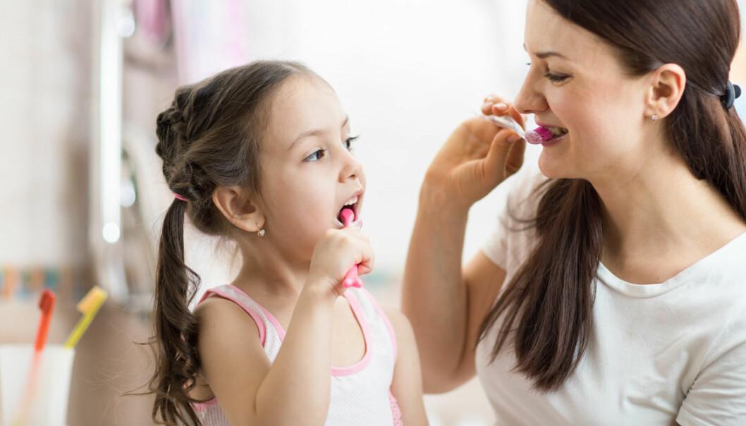 Mamma och barn borstar tänderna