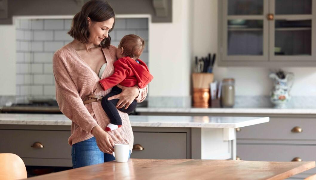 Mamma håller i sitt barn och har en bröstpump
