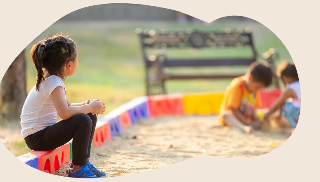 ensam flicka tittar på kamrater i sandlådan
