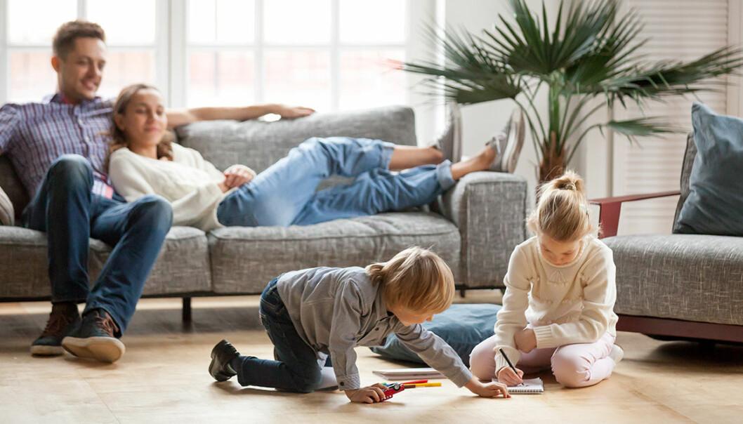 Familj i soffa med lekande barn på golvet