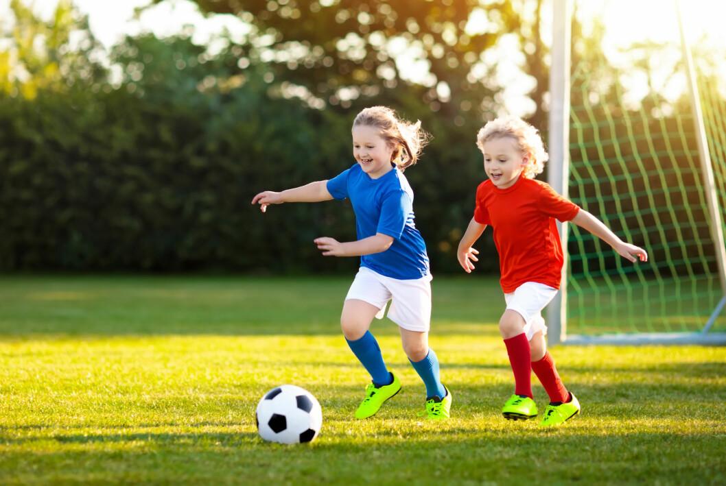 barns som spelar fotboll m