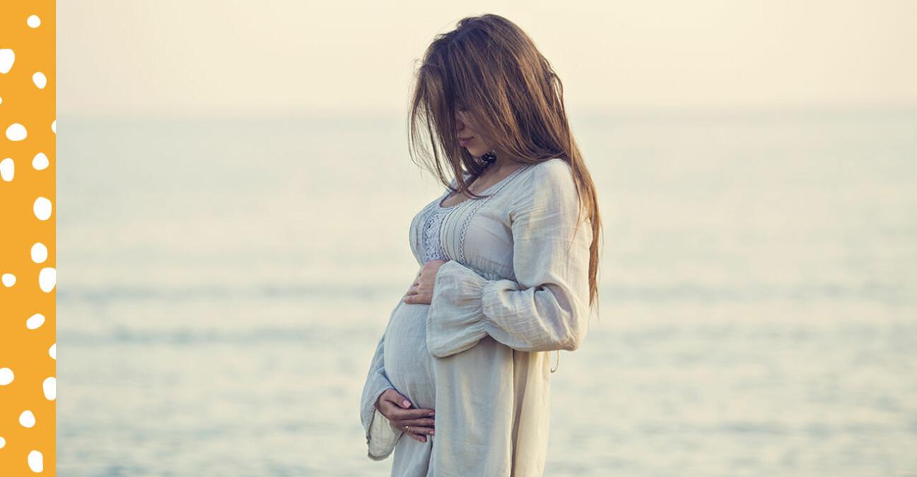 gravid kvinna håller om sin mage