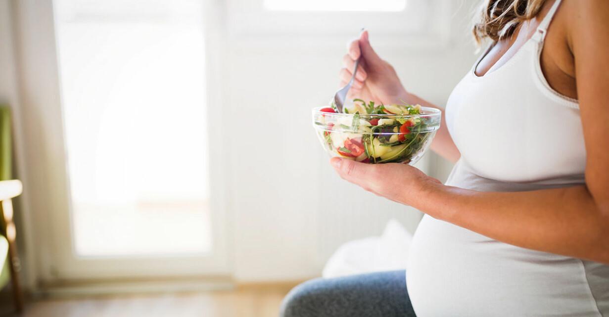 Gravid kvinna med skål sallad