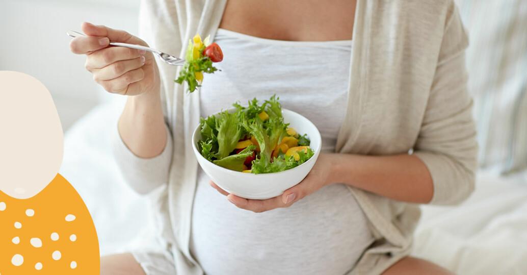 Gravid kvinna äter sallad