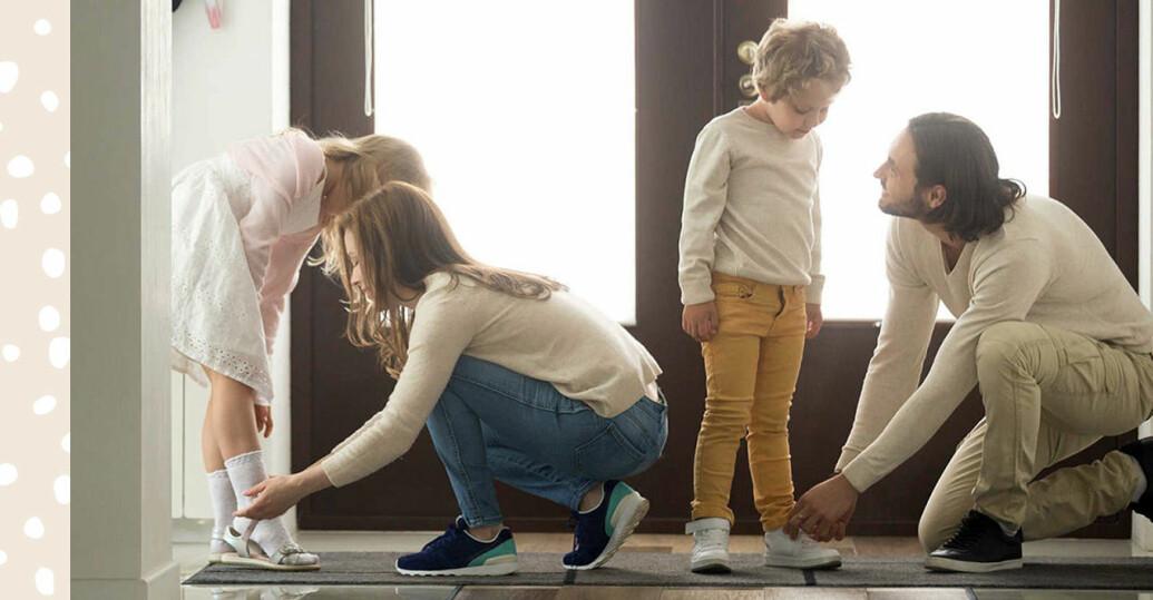Mamma och pappa hjälper barnen knyta skorna.