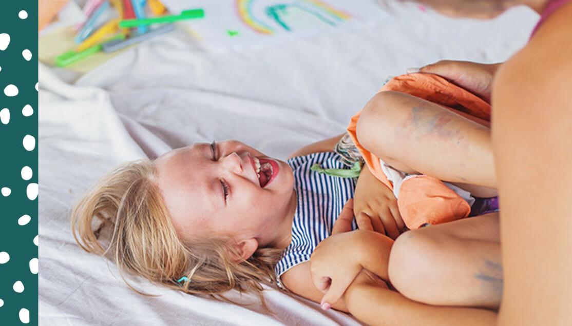 Barn blir kittlat. Ligger och skrattar.