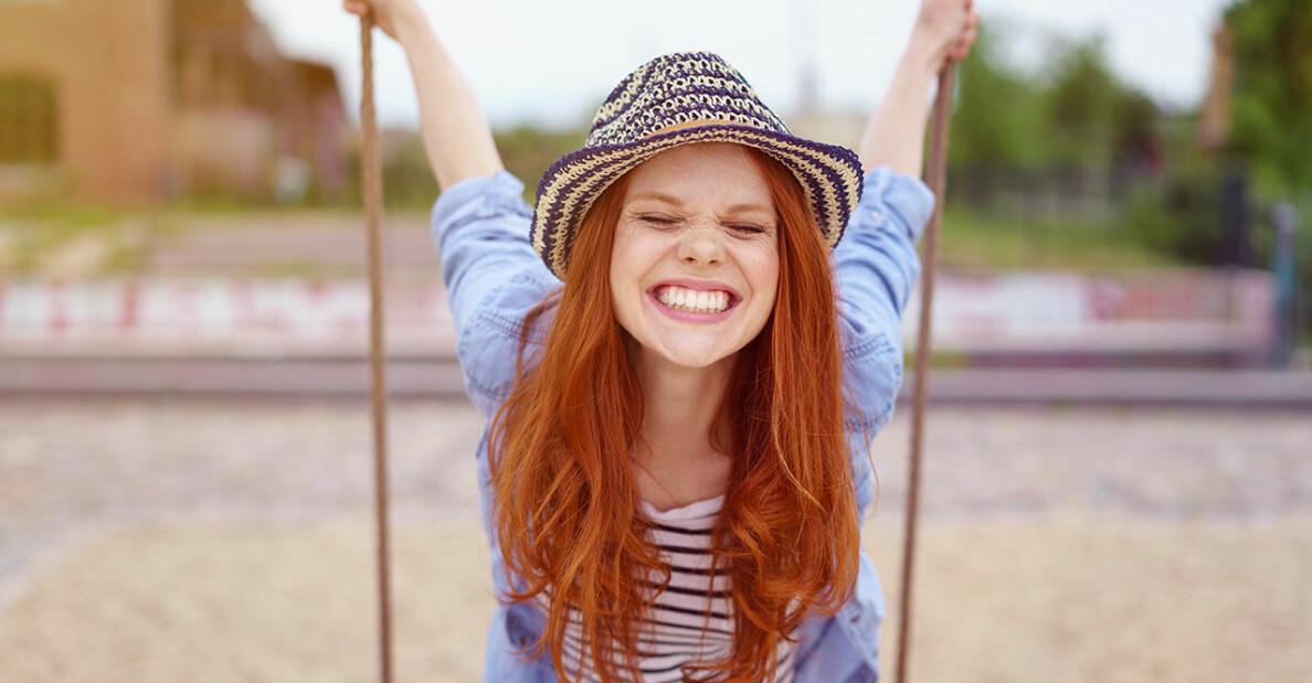 Ung kvinna som ler stort på en gunga.