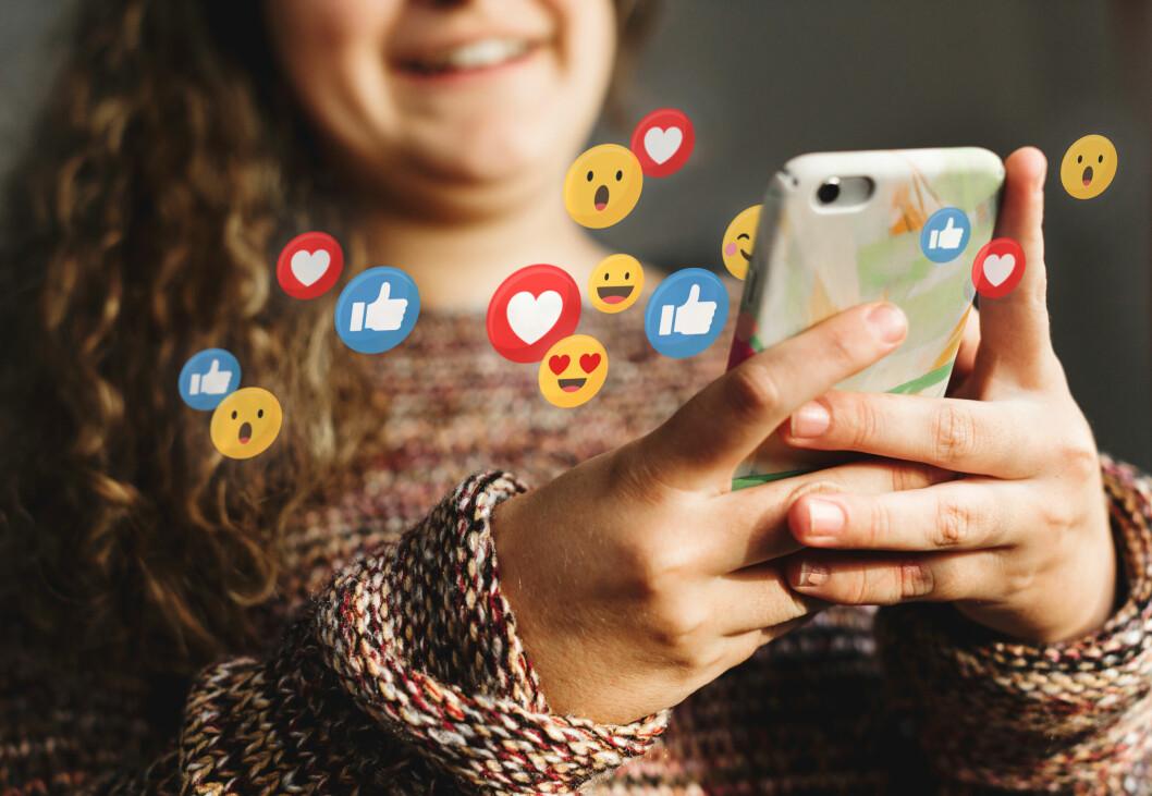 kvinna som håller i en mobil och använder sociala medier