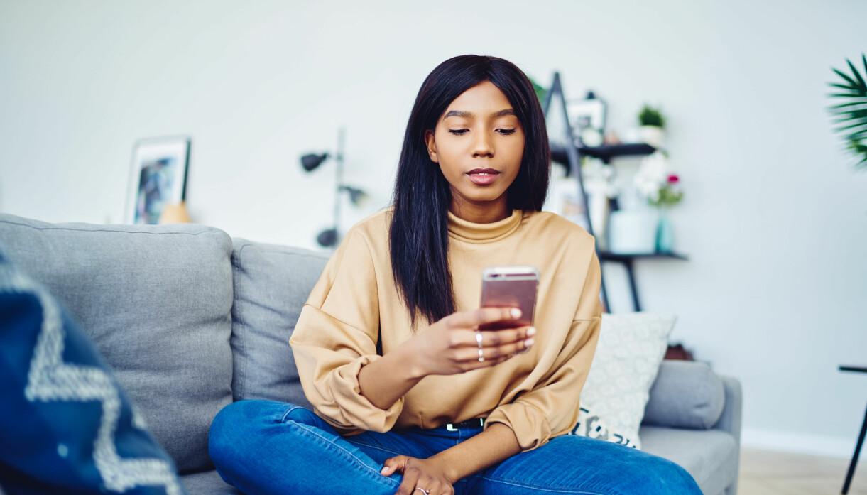 kvinna som tittar på mobilen hemma
