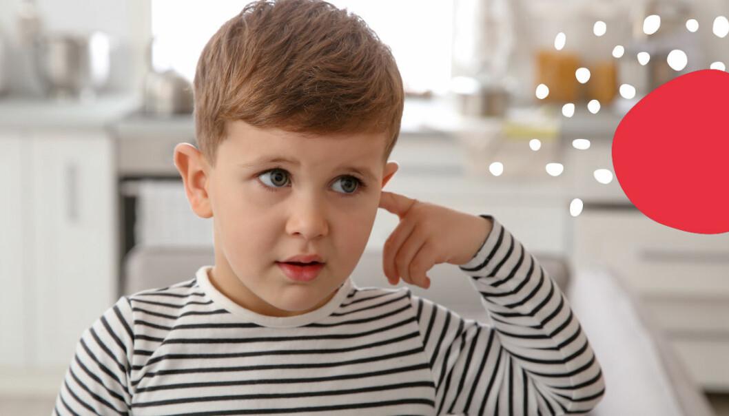 Liten pojke som pekar på sitt öra.