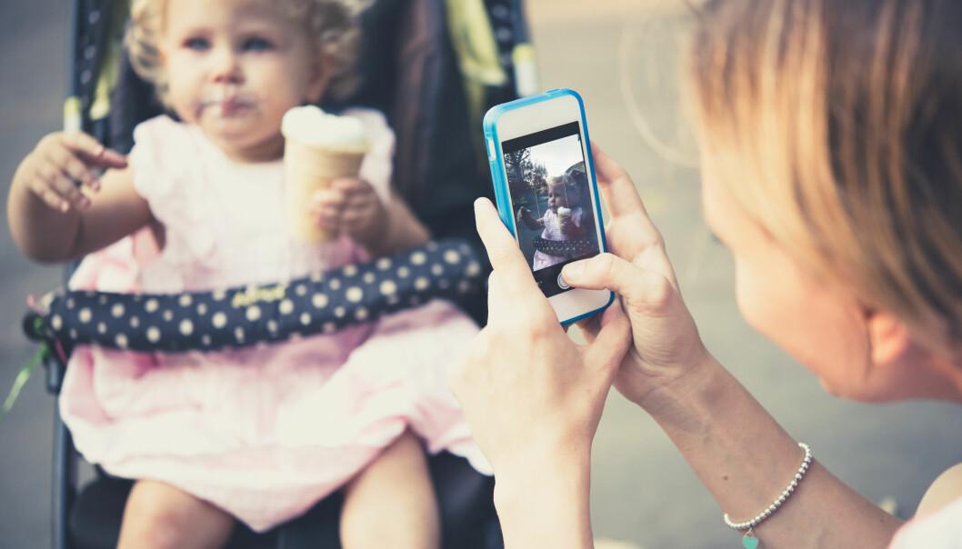 mamma fotar barn med mobilen