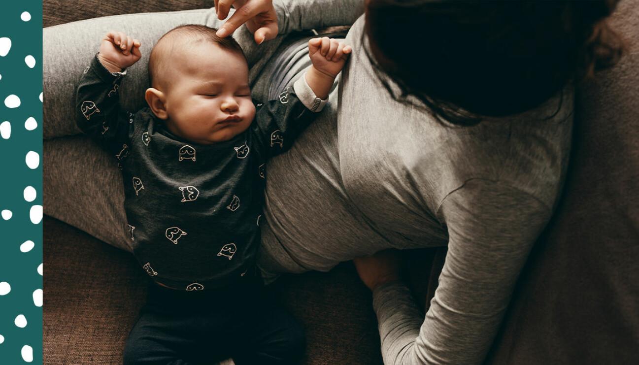 mamma med sovande bebis i knät