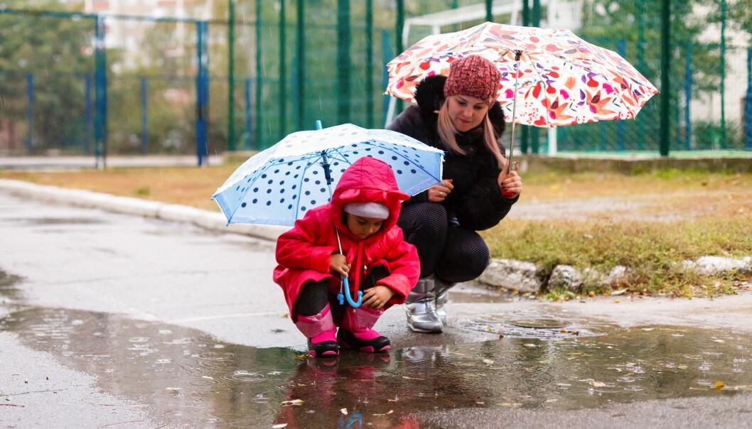 mamma och barn går i regn