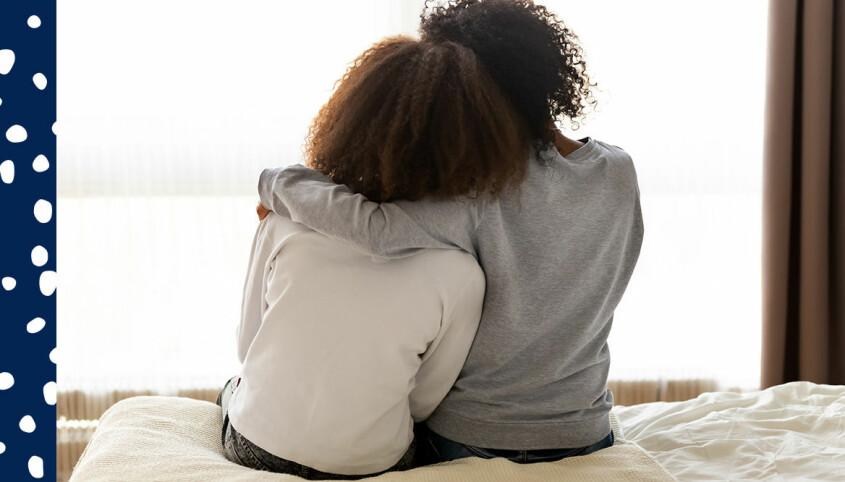 mamma och dotter pratar och kramas på sängen