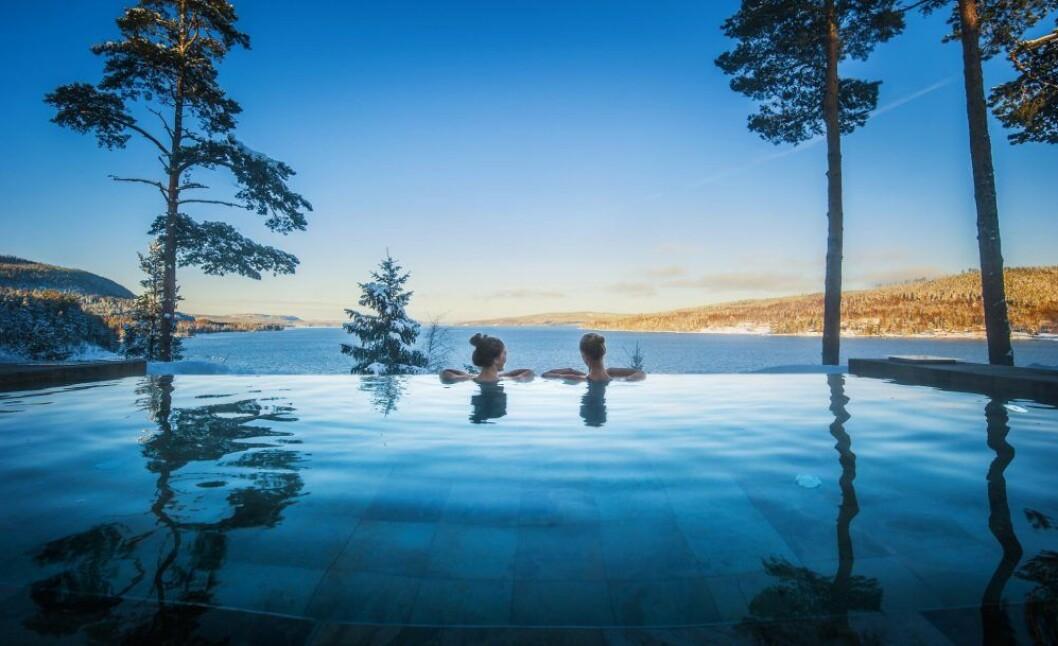 Två personer sitter i en pool och ser ut över vattnet och naturen