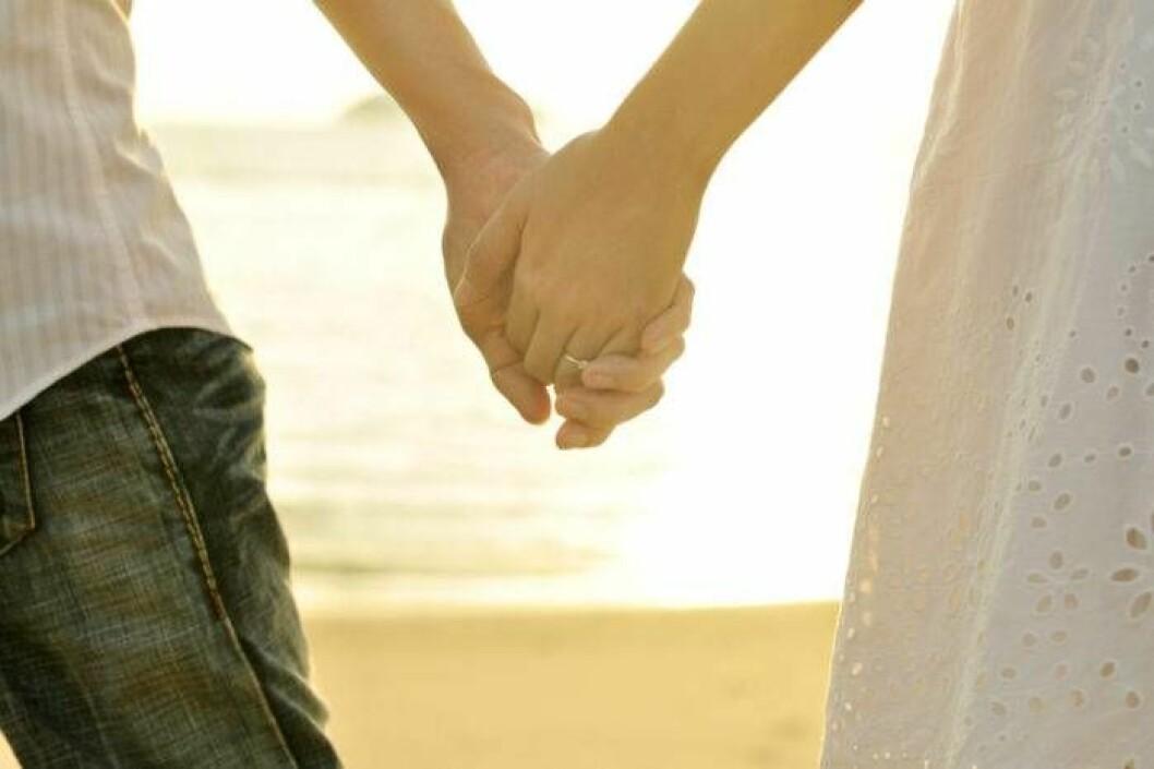 Kvinna och man i solnedgång, hand i hand.