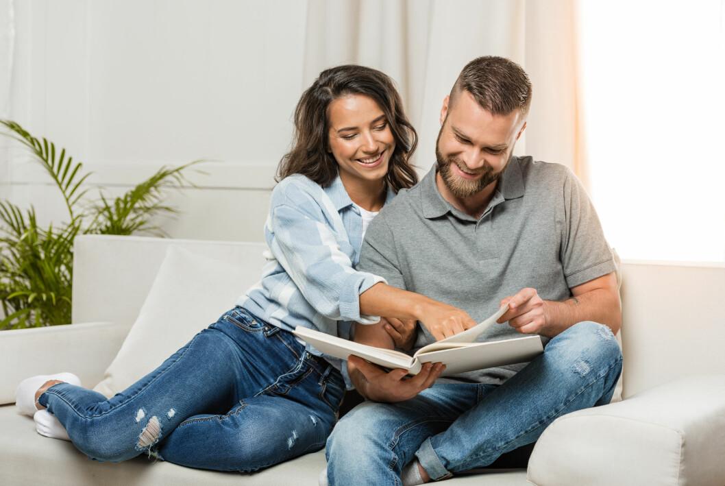 En man och en kvinna kollar i fotoalbum
