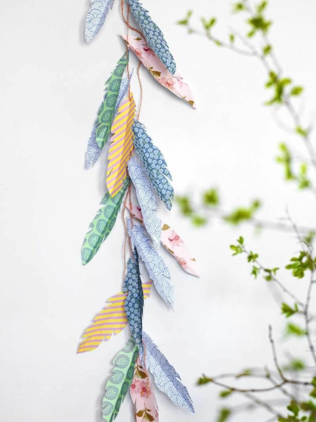 Gör fjädrar av papper och häng som en girlang.