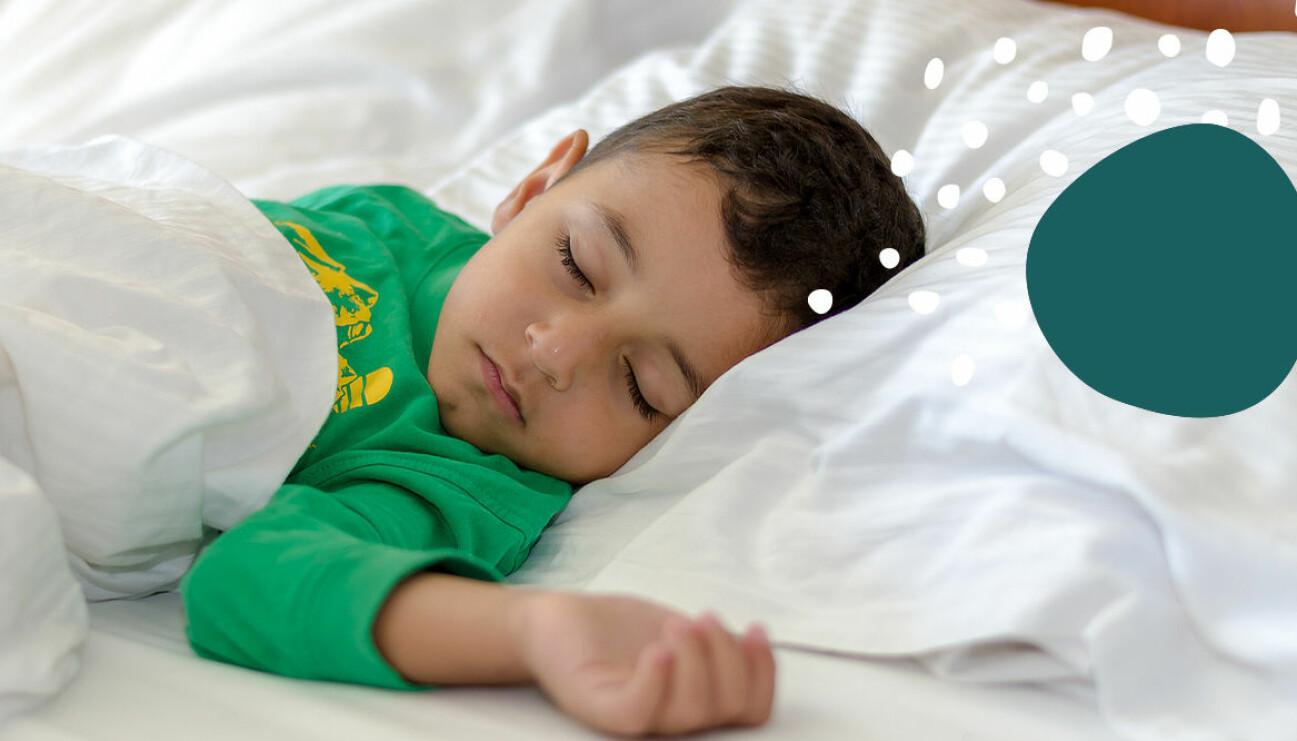 Pojke som sover i dubbelsäng med vita lakan.