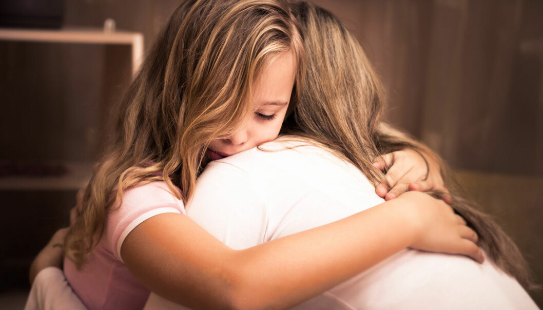 Kvinna kramar ledset barn