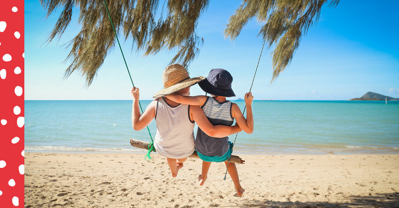 Barn sitter på gunga på strand