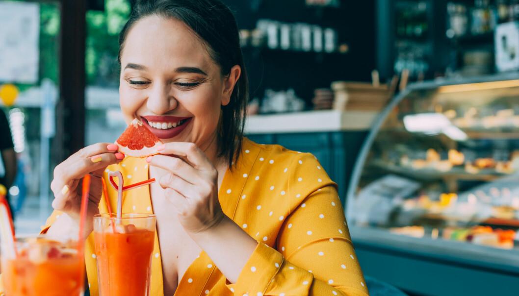 Kvinna i gul blus äter grapefrukt på kafe