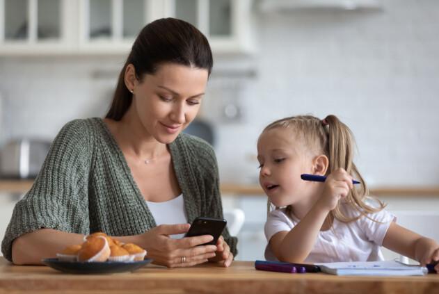 mamma och barn vid matbordet med mobiltelefon