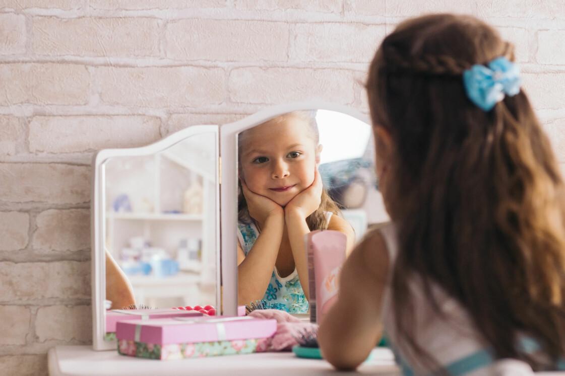 Flicka tittar sig i spegeln