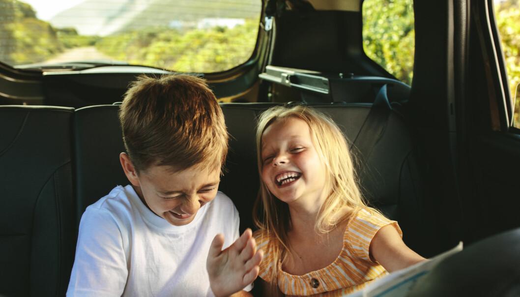 Två barn skrattar i bilen