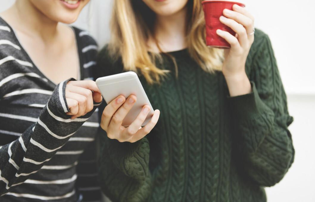 ungdomar som håller i mobil