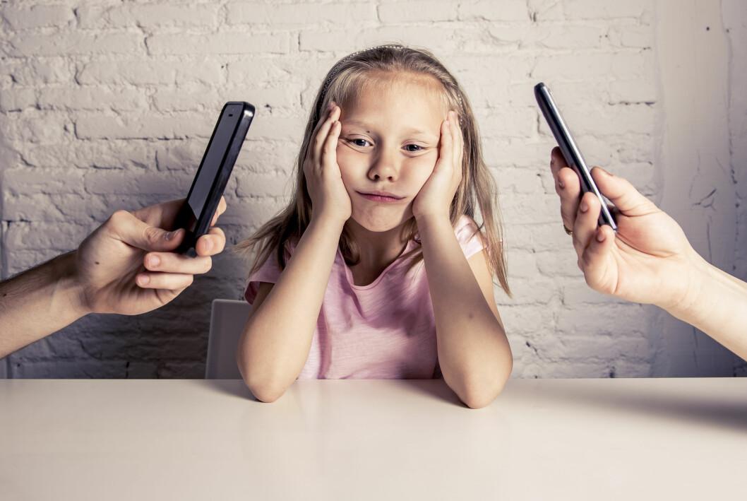 barn och föräldrar som håller i mobiltelefoner