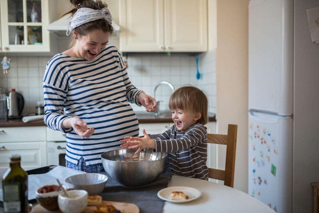 kvinna som är gravid bakar med sin son