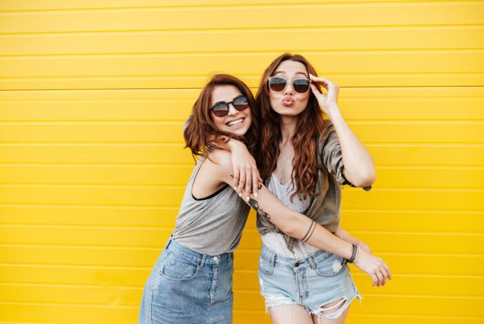 Två vänner med solglasögon och gul vägg