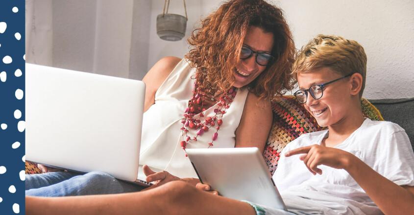 Förälder och ett barn tittar på varsin skärm