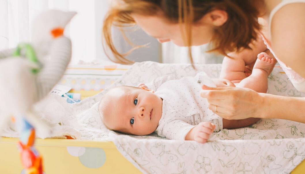 Skotbord med bebis och mamma som håller i bebis