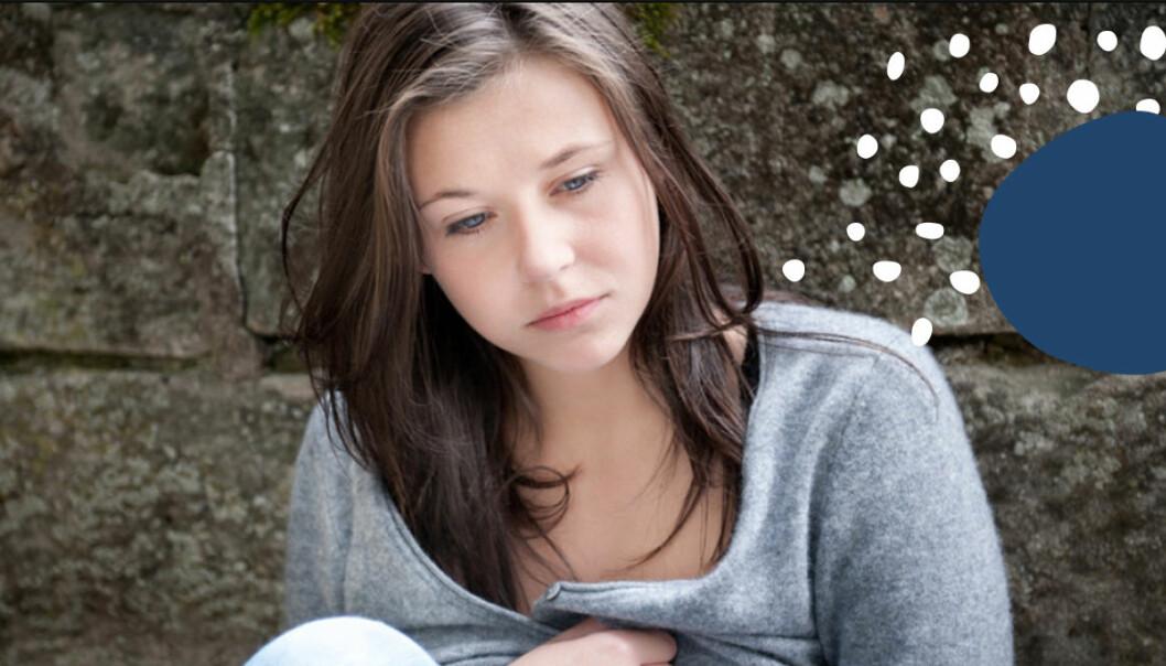 Ung tjej sitter vid vägg. Ser ledsen ut.