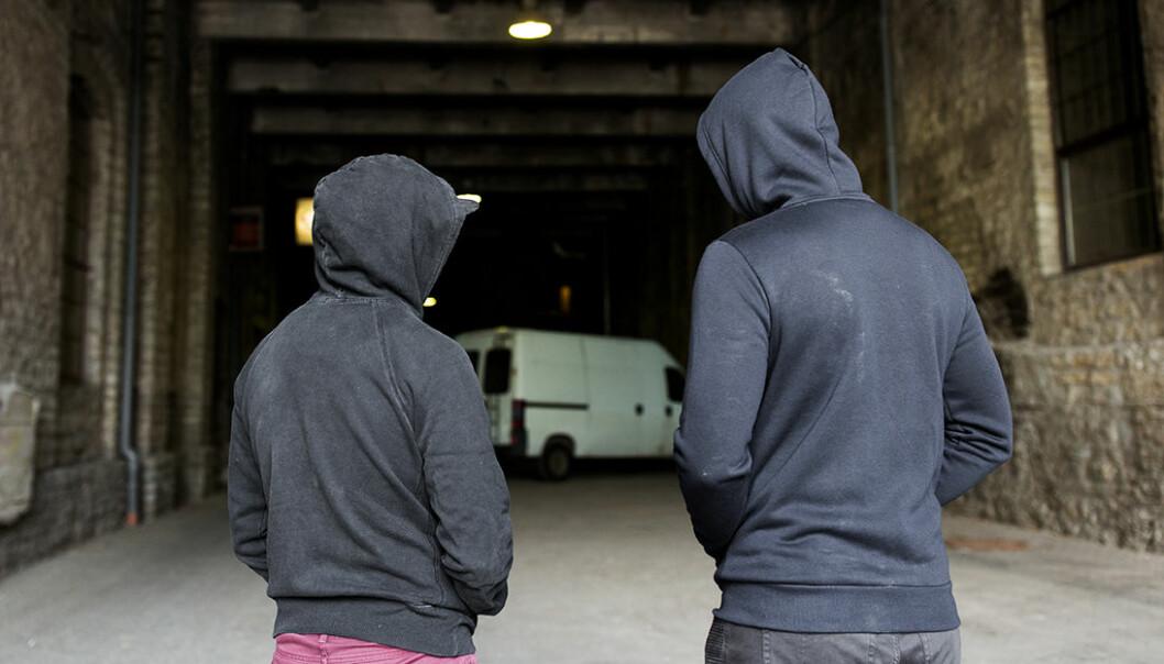 Två unga killar i hoodies står i mörk gång med en skåpbil som skymtar i bakgkrunden.
