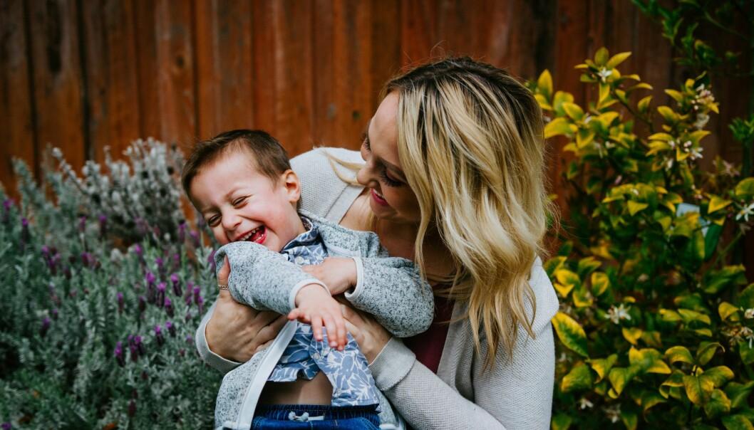 Ung blond kvinna busar med en liten pojke i en trädgård