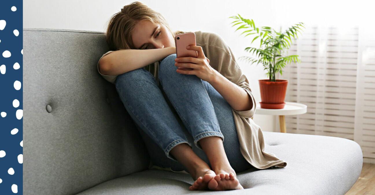 Ung kvinna med mobil i en soffa