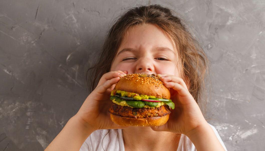 Barn tar bett av vegetarisk hamburgare.